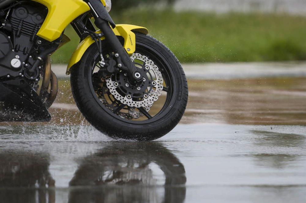 Conducción en moto con asfalto mojado